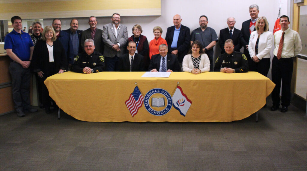 Pictured from left seated: Marshall County Chief Deputy Sherriff William Helms, Marshall County Schools Assistant Superintendent Woody Yoder, Benwood Mayor Edward Kuca Jr., Marshall County Schools Superintendent Shelby Haines and Marshall County Sherriff Kevin Cecil. From left standing: Marshall County AFT President Josh Gary, Marshall County Clerk Jan Pest, WV Delegate Lisa Zukoff, Marshall County Assessor Terry McDiffitt, Marshall County Commissioner Scott Varner, McMechen Mayor David Goddard, Moundsville Mayor Phil Remke, Marshall County BOE member Christi Robison, Marshall County BOE member Brenda Coffield, Marshall County Commissioner Mike Ferro, Marshall County BOE member Dr. Duane Miller, Marshall County Schools BOE President John Miller, Marshall County Commissioner John Gruzinskas, JM Principal Cassie Porter and Marshall County Education Association President Matt Mandarino.
